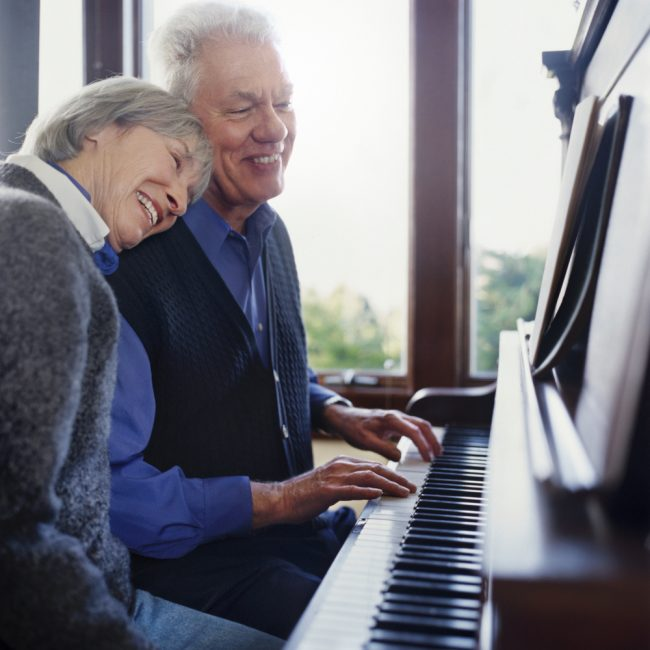 Older couple playing the piano in their home in Dallas, TX
