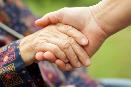Older patient holding a doctor's hand in Dallas, TX