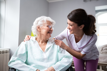 Older woman smiling with nurse at home in Dallas, TX